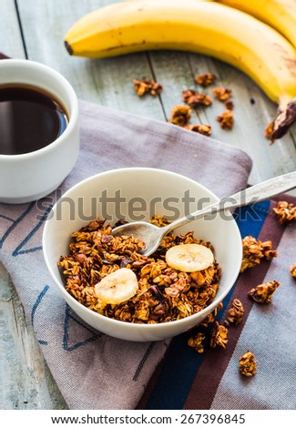 banana granola with nuts, figs and honey in a white piala, clean eating - stock photo