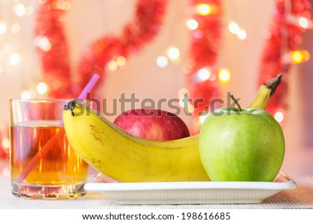 Banana, green and red apples on white plate and glass of apple juice (birthday party) - stock photo