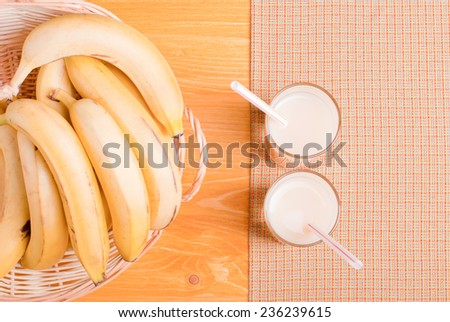 banana juice in a glass on a yellow napkin on the table next to bananas in a wicker basket top view - stock photo