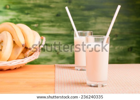 banana juice in two cups on a yellow table with a napkin on zalenom background bananmi side view