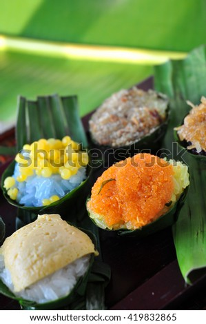 Banana leaf cup of sticky rice Thai dessert on wooden tray - stock photo