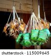 banana leaf packages containing a fish snack for sale in asia on a market - stock photo