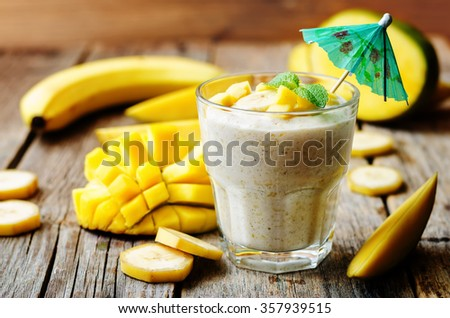 banana mango smoothie on a dark wood background. toning. selective Focus - stock photo