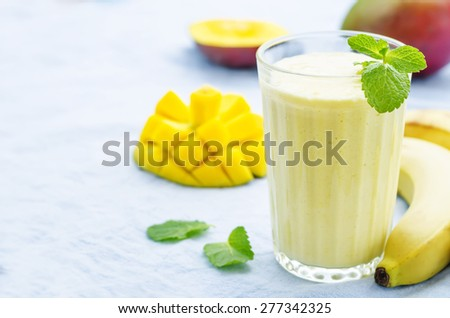 banana mango smoothies on a blue background. the toning. selective focus - stock photo