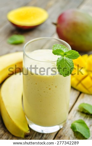 banana mango smoothies on a dark wood background. the toning. selective focus