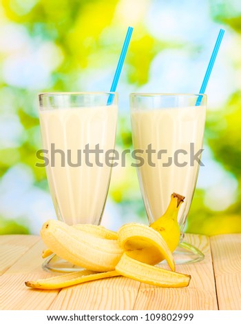 Banana milk shakes on wooden table on bright background - stock photo