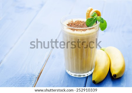 banana milkshake on a blue wood background. tinting. selective focus - stock photo