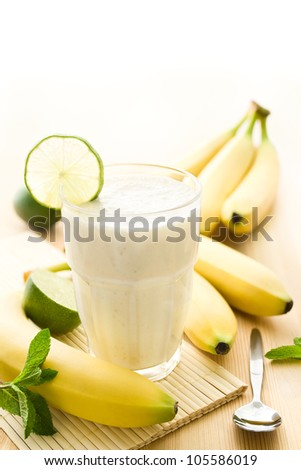 Banana milkshake or smoothie with bananas on wood - stock photo