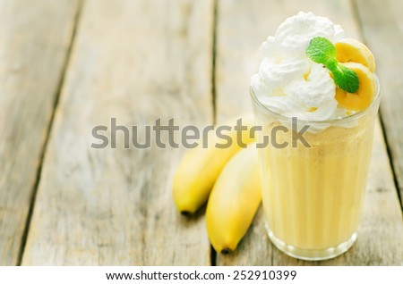 banana milkshake with whipped cream on a dark wood background. tinting. selective focus - stock photo