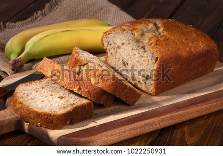 Banana nut sweet bread sliced on a wooden cutting board