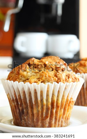 Banana oat muffins in foreground; de-focused espresso machine in background - stock photo