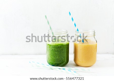 Banana-orange and banana-kale smoothie in glasses