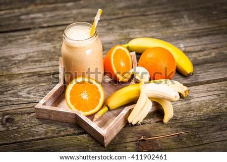 Banana orange milkshake on wooden table - stock photo