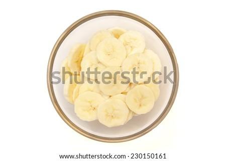 Banana slices on bowl on white background viewed from above - stock photo