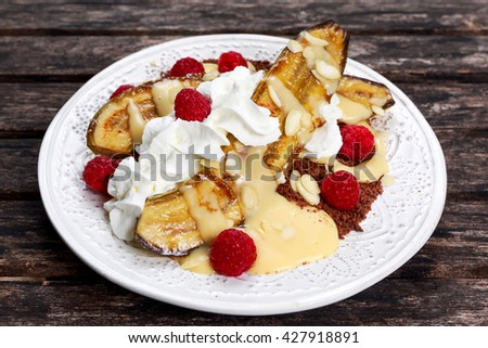 Banana slip dessert with raspberries, mint under whipped cream - stock photo