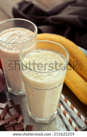 Banana smoothie in glass with fresh fruits and chocolate on wooden background - stock photo