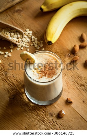 Banana smoothie with cinnamon, peanut butter and oat flakes on wooden background, top view food. Healthy vegan breakfast - stock photo