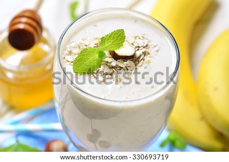 Banana smoothie with oats and hazelnuts on a light wooden table.