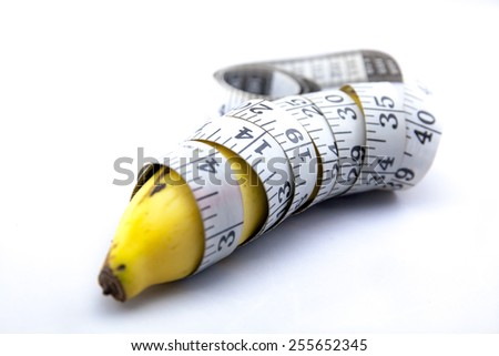 Banana wrapped up with Measure Tape - stock photo