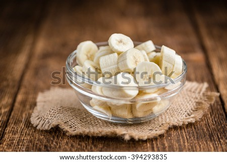 Bananas (chopped) on an old wooden table (selective focus) - stock photo