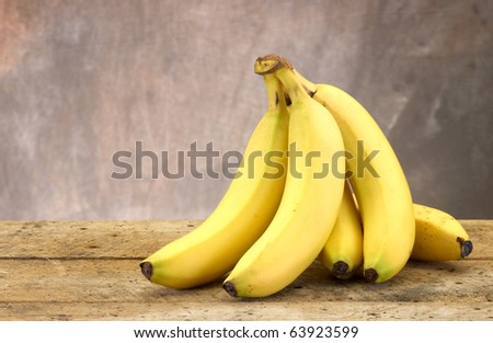 Bananas on and old vintage table top with modeled tan background for a rustic feel and copy space - stock photo