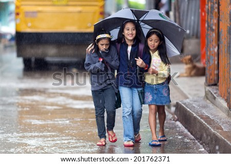 BANAUE, PHILIPPINES, DECEMBER 03 : Little girls are walking under the rain sheltering with an umbrella in the street of Banaue village, north Luzon, Philippines, on december 03, 2013 - stock photo