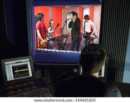 Band in recording studio with technician in foreground - stock photo