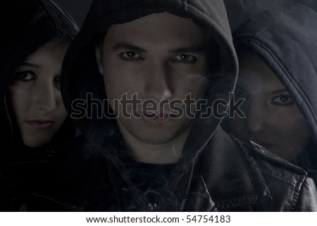 Band members in white black soft contrast with smoke around them in darkness - stock photo