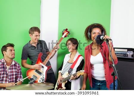 Band Members Performing In Recording Studio - stock photo