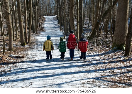 Band of boys follow the snow covered path through the woods - stock photo