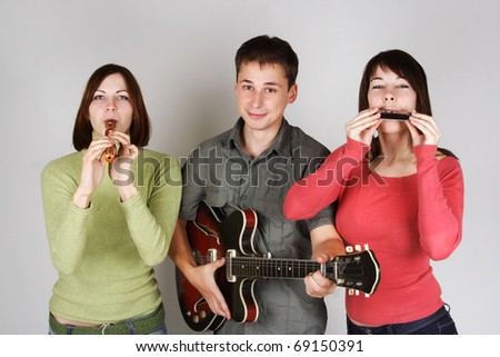 band of two young women and man playing on flute, harp and guitar - stock photo