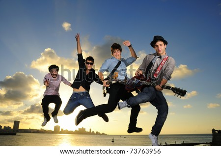 Band of young male musicians jumping with instruments against sunset sky background - stock photo