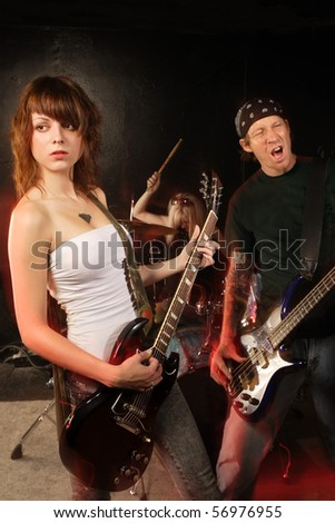 Band playing on a stage. Female guitarist, male bassist and female drummer. Shot with strobes and slow shutter speed to create lighting atmosphere and blur effects. Slight motion blur on performers. - stock photo