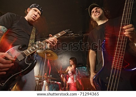 Band playing on a stage. Guitarist, bassist and female drummer. Shot with strobes and slow shutter speed to create lighting atmosphere and blur effects. Slight motion blur on performers. - stock photo