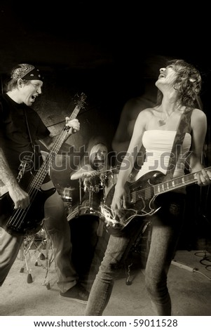 Band playing on a stage. Male bassist with female guitarist and drummer. Shot with strobes and slow shutter speed to create lighting atmosphere and blur effects. Slight motion blur on performers. - stock photo
