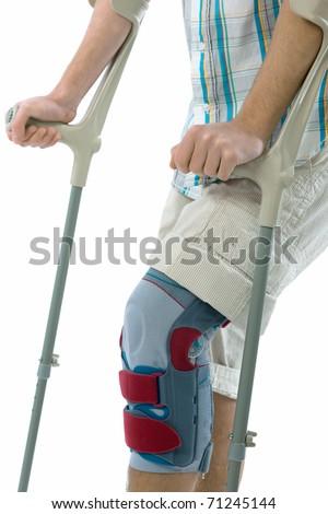 Bandage on knee of man's on crutches - stock photo
