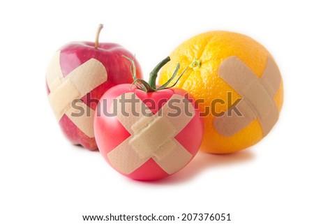 Bandaged apple, tomato, and orange to promote healthy living - stock photo