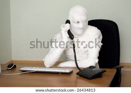 Bandaged boss calling on telephone in office - stock photo