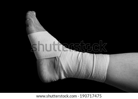 Bandaged leg, foot sprain, monochrome image - stock photo