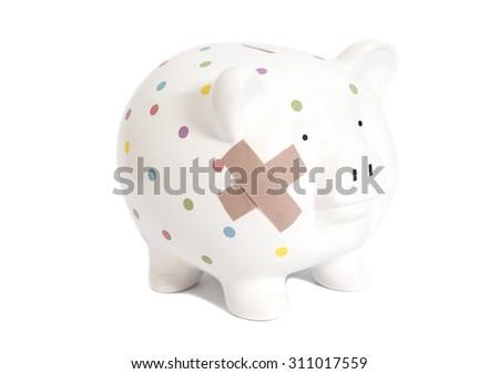 Bandaged piggy bank isolated on white - stock photo