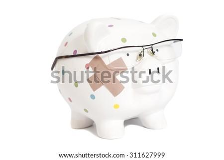 Bandaged piggy bank with eyeglasses isolated on white - stock photo