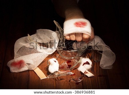 Bandaged wounded by a hand against the dark wood. - stock photo