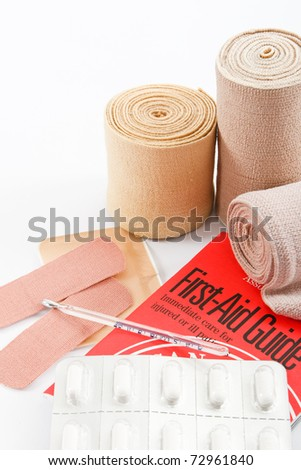 Bandages, pain killer tablets and knowledge are essential elements in a first aid kit - stock photo