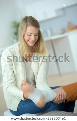 Bandaging her friend's leg - stock photo