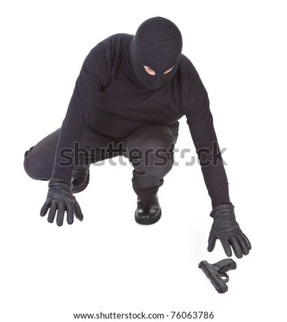 bandit is trying to recover his weapon on white background - stock photo