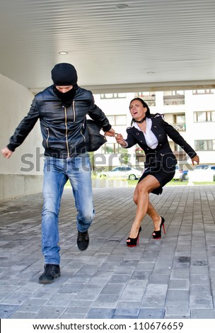 Bandit stealing businesswoman bag in the street - stock photo