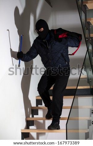 Bandit wearing a mask with crowbar on stairs - stock photo