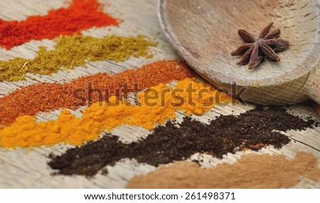 bands of different spices powder and anise in  spoon on wooden  background - stock photo
