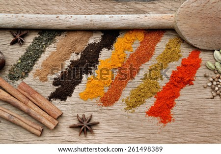bands of different spices powder, anise and cardamom and spoon on wood background - stock photo
