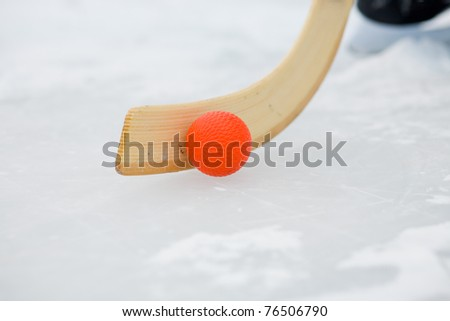 Bandy stick and Bandy ball on ice, skates in the background - stock photo